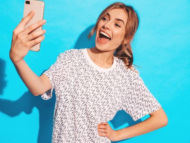 写真selfieを撮る陽気な若い女性の肖像画。スマートフォンのカメラを保持している美しい少女。スタジオの青い壁に近いポーズモデルの笑みを浮かべてください。びっくりしたモデル