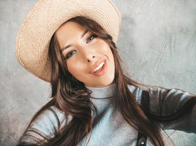 インスピレーションと写真selfieを取り、現代の服と帽子を着て陽気な若い女性の肖像画。