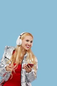 Портрет жизнерадостной молодой женщины нося вскользь изолированную серебряную куртку, слушающ к музыке с наушниками, танцуя. ух ты и удивленное лицо