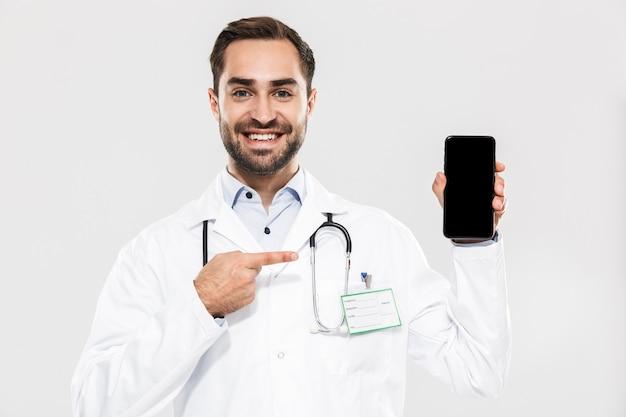 Портрет веселого молодого врача со стетоскопом, работающего в клинике и держащего мобильный телефон, изолированного над белой стеной