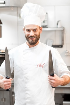 レストランの厨房でナイフで制服を着たシェフの肖像画