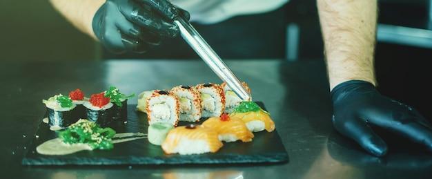 Портрет шеф-повара украшать суши и роллы на кухне