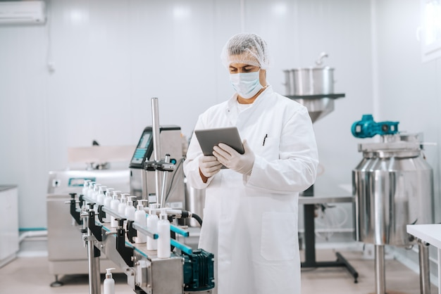 Портрет химика в стерильной форме с помощью планшета, стоя рядом с машиной с жидким мылом
