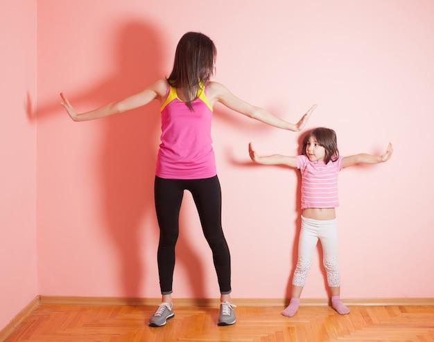Портрет ребенка и матери, которые вместе делают физические упражнения дома