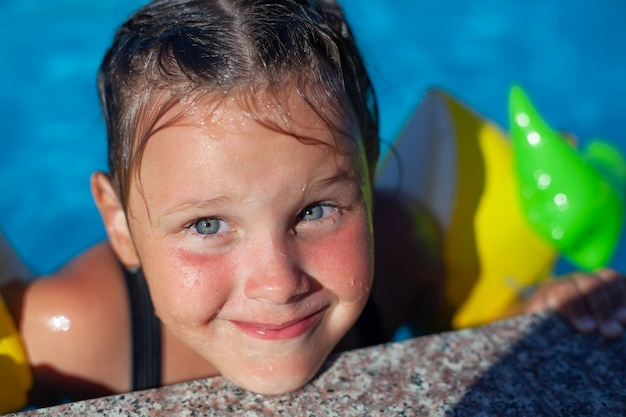 プールのそばの子供の肖像濡れた髪の小さな幸せな女の子は、プールの横に顔を作り、戦争を楽しんでいます...