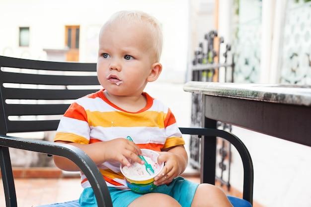 Портрет ребенка есть мороженое. на улице в кафе
