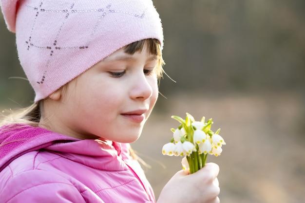 Портрет ребенка девушка держит букет весенних подснежников цветы.