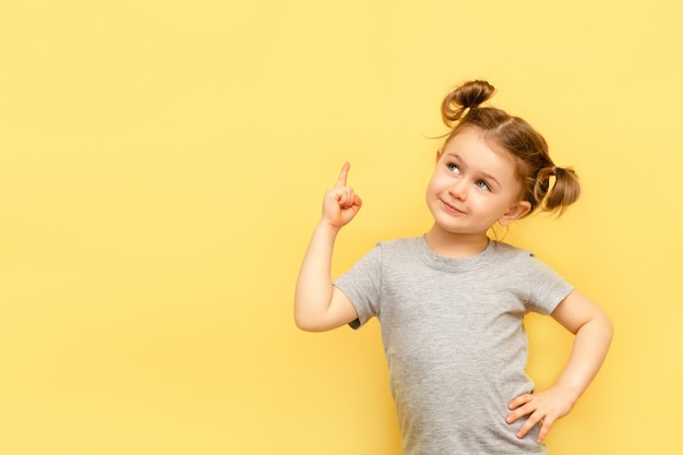 黄色の壁に隔離された上に指を指している子供の女の子の肖像画