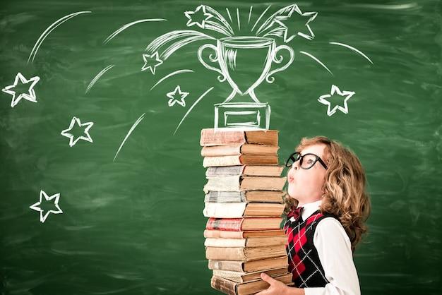 칠판에 교실에서 어린이의 초상화입니다. 수업 시간에 책을 가진 아이. 성공, 아이디어 및 승리 개념. 학교로 돌아가다