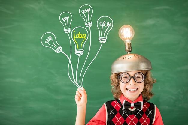 Портрет ребенка в классе. малыш с игрушечной гарнитурой виртуальной реальности в классе. успех, идея и творческая концепция. обратно в школу