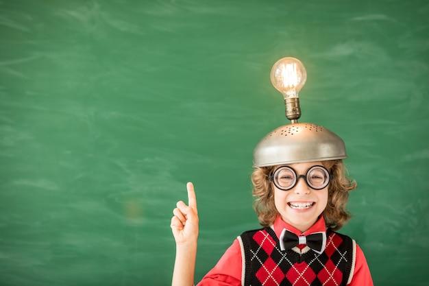 Портрет ребенка в классе. малыш с игрушечной гарнитурой виртуальной реальности в классе. концепция успеха, идеи и инновационных технологий. обратно в школу