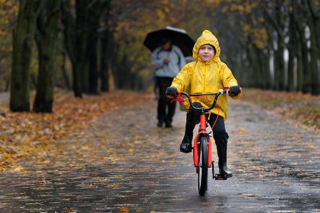 Портрет ребенка на велосипеде под дождем. мальчик в желтом плаще катается в парке