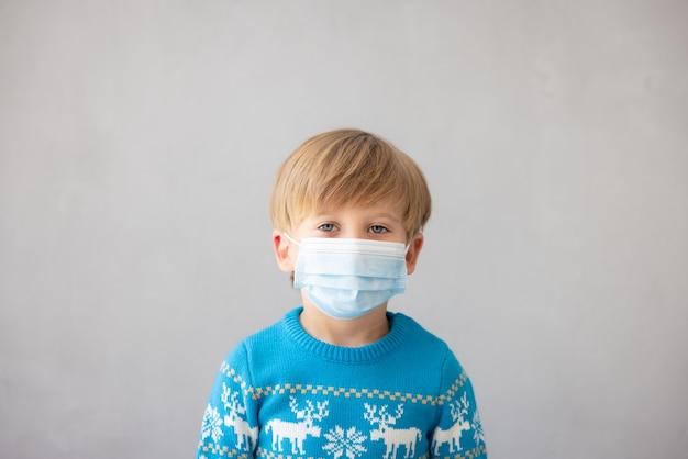 코로나바이러스 covid19 전염병 개념 동안 의료용 마스크 크리스마스를 쓴 아이의 초상화