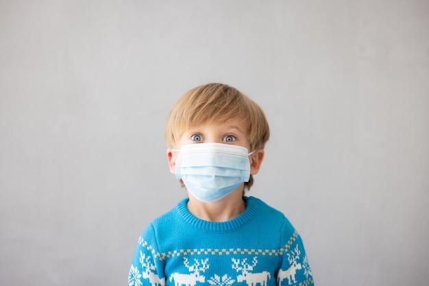 코로나바이러스 전염병 개념 동안 의료용 마스크 크리스마스 휴가를 쓴 아이의 초상화