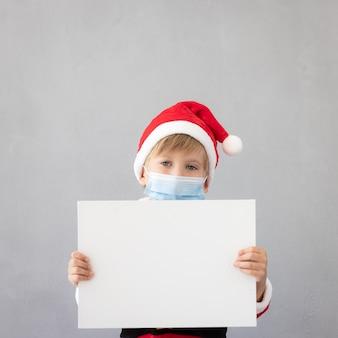 의료용 마스크를 쓴 아이의 초상화 카피 공간이 있는 빈 배너를 들고 있는 아이