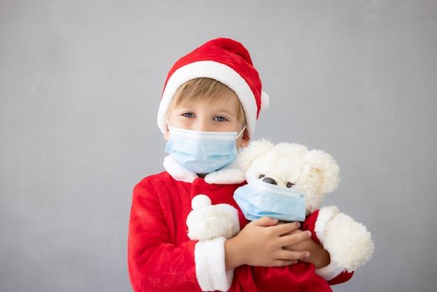 의료용 마스크를 쓰고 있는 아이의 초상화 테디베어를 들고 있는 아이