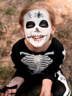 ハロウィーンの衣装を持つ子供の肖像画
