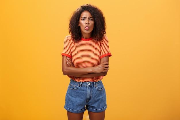곱슬 머리 혀와 교차 팔을 보여주는 유치 한 불쾌하거나 불쾌 하 게 젊은 아프리카 계 미국인 여자의 초상화.