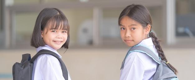 制服とバックパックを身に着けた子供たちの肖像画19回の検疫と封鎖の後に学校に戻るカメラを見てください。学校に戻るコンセプトストックフォト