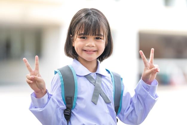 制服とバックパックで子供の学生の肖像画学校に戻るカメラを見て