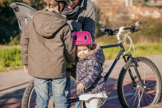 손상된 자전거 타이어를 수리하는 동안 아버지를 바라보는 보안 헬멧을 쓴 아이들의 초상화
