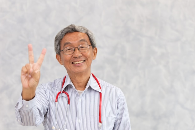 テキストのためのスペースを持つ中国人医師健康な老人アジアの高齢者の立っている笑顔の手の勝利のサインの肖像画。