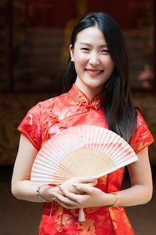Портрет китаянки в китайской одежде позирует у цементной двери