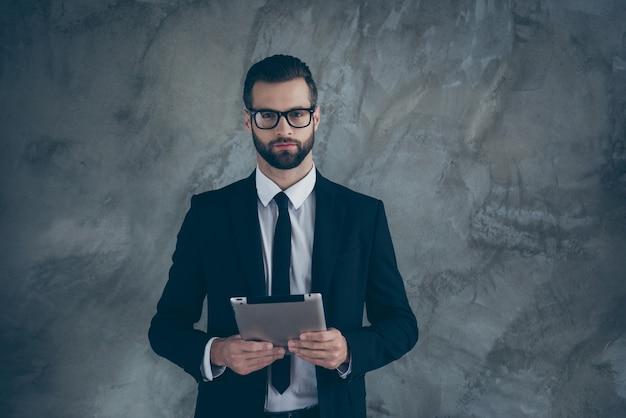 Портрет умного умного парня, бизнесмена, держащего свой планшет, хочет начать презентацию стартапа в модном костюме, изолированном над серой стеной