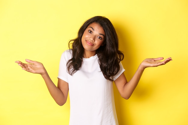 Портрет невежественной, красивой афро-американской девушки, пожимающей плечами и улыбающейся, извиняющейся за то, что она не знает, стоя на желтом фоне.