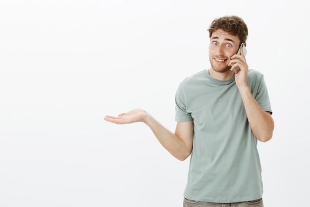 Портрет невежественного красивого кавказского мужчины со светлыми волосами, пожимающего плечами с раскинутой ладонью и говорящего по смартфону, не подозревая и допрашивая