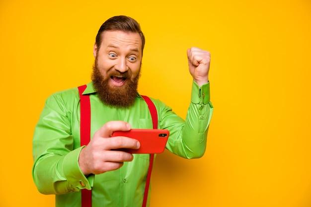 Портрет конкурентоспособного веселого восторженного человека, использующего смартфон, играть в видео онлайн-игру, выиграть гонку, кричать, да, поднять кулаки, носить красные подтяжки, зеленую рубашку, изолированную над ярким цветом