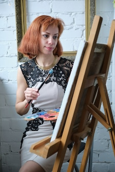 アートパレットを保持し、自宅でブラシでキャンバスに絵を描く集中した美しい女性画家の肖像画