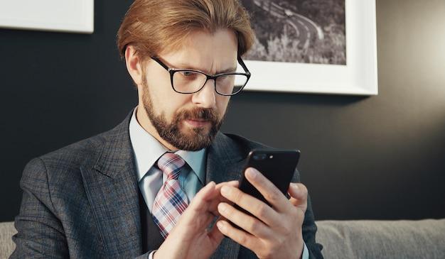 Портрет сосредоточенного бизнесмена, держащего мобильный телефон, смотрящего на экран, в помещении