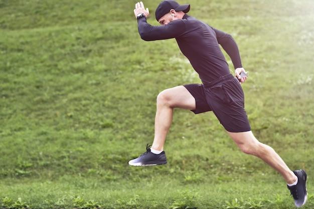 반바지와 운동화를 입고 힘 스포츠맨으로 가득한 집중 자신감 근육의 초상화.