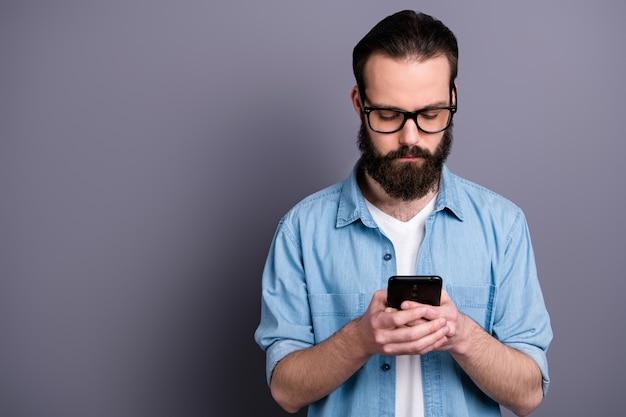 集中フリーランサーブロガー男の肖像は、スマートフォンを使用してソーシャルメディア情報を読むクライアントとのチャット同僚は灰色の壁に隔離された見栄えの良いジーンズの服を着ています