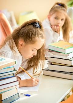 숙제를하는 집중된 소녀의 초상화를 쓰는 동급생 동안