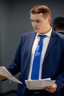사무실에서 문서를 가지고 직장에서 일하는 집중된 변호사의 초상화