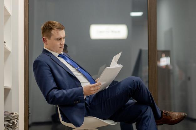사무실에서 문서와 함께 직장에서 일하는 집중된 변호사의 초상화