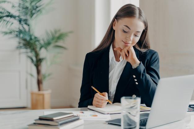 Портрет сосредоточенной, думающей молодой кавказской деловой женщины в черном строгом костюме, сидящей и записывающей в записной книжке перед ноутбуком на белом столе с бантом на размытом фоне