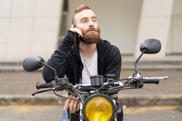 Портрет сосредоточенного молодого байкера разговаривает по мобильному телефону