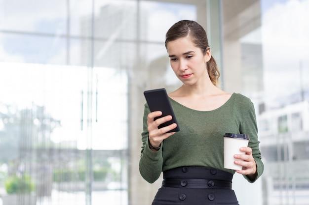 集中した若い女性の肖像画、電話でメッセージを読む