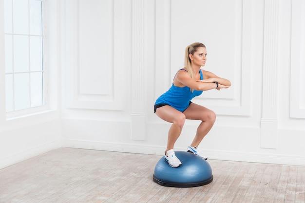 검은 반바지와 파란색 탑을 입은 집중력 있는 아름다운 젊은 운동 금발 여성의 초상화는 체육관에서 bosu 균형 트레이너에서 운동을 하고, 피트니스 공에 쪼그리고 앉아 균형을 잡고 있습니다.