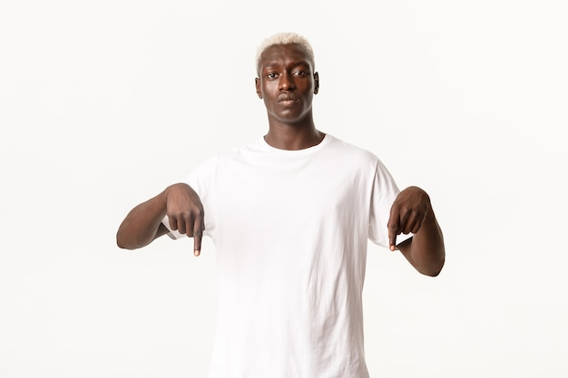 心配しているアフリカ系アメリカ人の金髪の男の肖像画、指を下に向けて真面目なカメラを見て