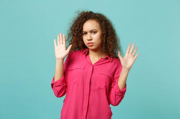 スタジオで青いターコイズブルーの壁の背景に分離された手のひらを示す、カジュアルな服を着て手を上げて心配しているアフリカの女の子の肖像画。人々の誠実な感情のライフスタイルの概念。コピースペースをモックアップします。