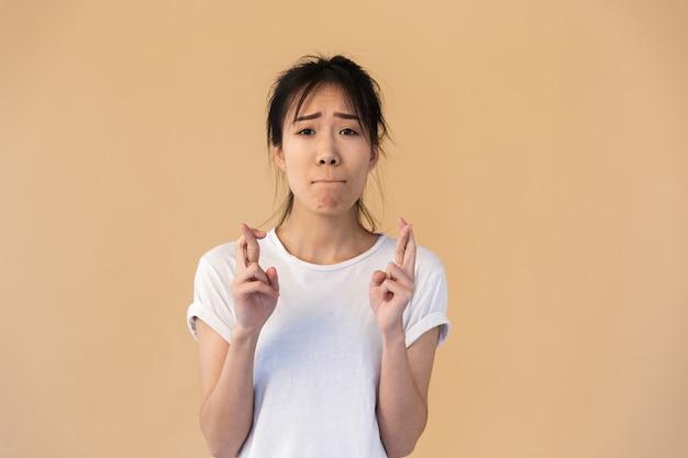神を懇願する基本的なtシャツを着ている心配しているアジアの女性の肖像画は、スタジオでベージュの壁の上に分離された指を交差させてください