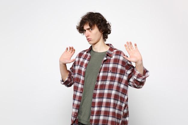 スタジオで白い壁の背景に孤立した手のひらを示して、手を上げてカジュアルな服を着て心配している当惑した若い男の肖像画。人々の誠実な感情、ライフスタイルのコンセプト。コピースペースをモックアップします。