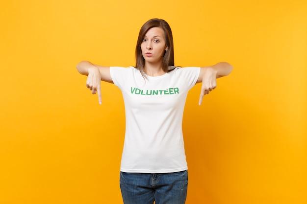 黄色の背景に分離された碑文の緑のタイトルボランティアが書かれた白いtシャツで心配している穏やかな深刻な若い女性の肖像画。自主的な無料支援支援、チャリティーグレイスワークコンセプト