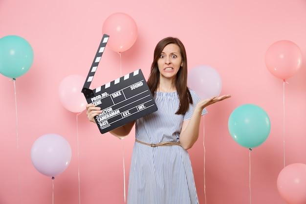 Портрет обеспокоенной неудовлетворенной женщины в синем платье, раскинувшей руки, держащей классический черный фильм, делающий с 'хлопушкой' на розовом фоне с красочными воздушными шарами. концепция вечеринки по случаю дня рождения.