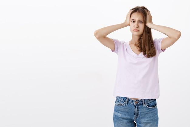Портрет обеспокоенной сытой и обеспокоенной женщины в повседневной футболке, держащей руки за голову, выглядящей расстроенной и измученной, находящейся в неприятной ситуации у серой стены