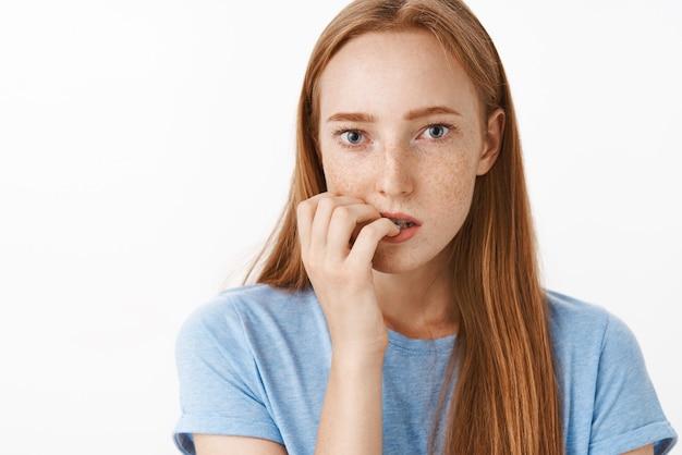 緊張した感情から爪を噛んでそばかすがあり、喫煙の罰を待っているパニックを抱えている懸念の焦点を当てた美しい生姜少女の肖像画